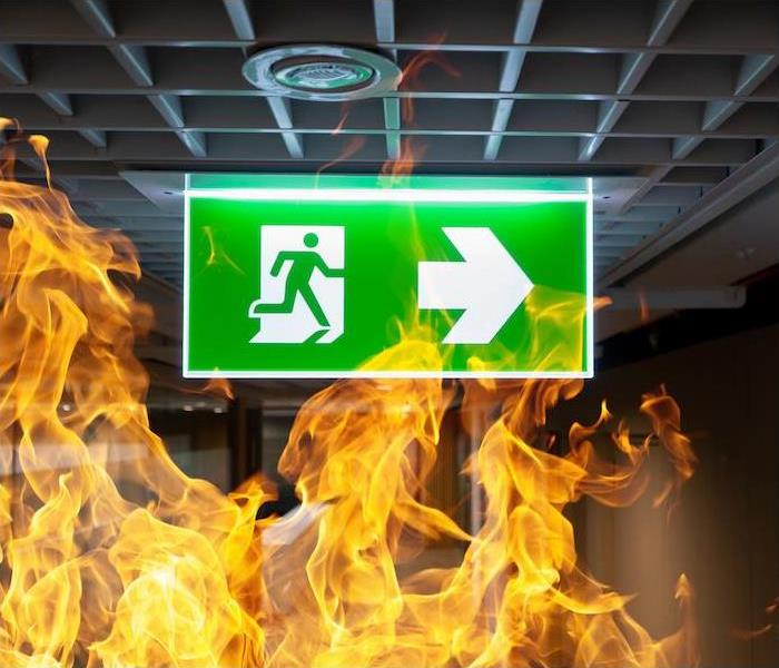 Photo is showing a fire in a commercial building with a green exit sign with an arrow showing which direction the exit is.