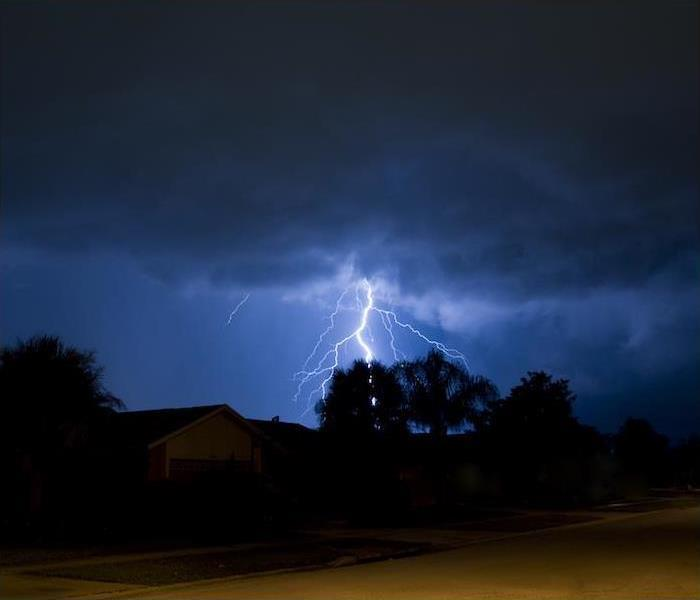 Photo is showing lightening striking at night behind a house and trees